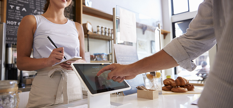 Customer using touch screen to make payment at a coffee